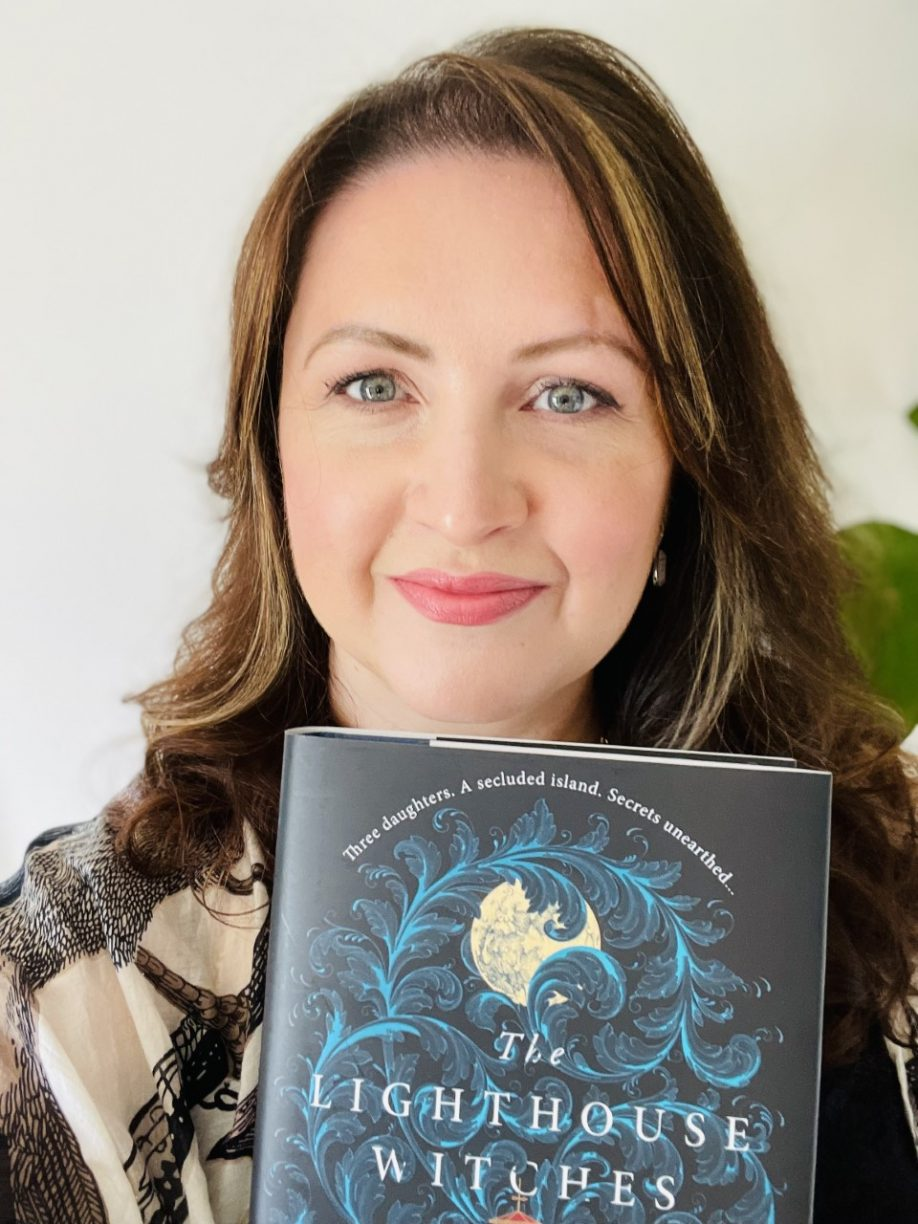 CJ Cooke faces the camera. She is a white woman with brown shoulder length hair and blue-green eyes, and is smiling. She holds a copy of her novel THE LIGHTHOUSE WITCHES.