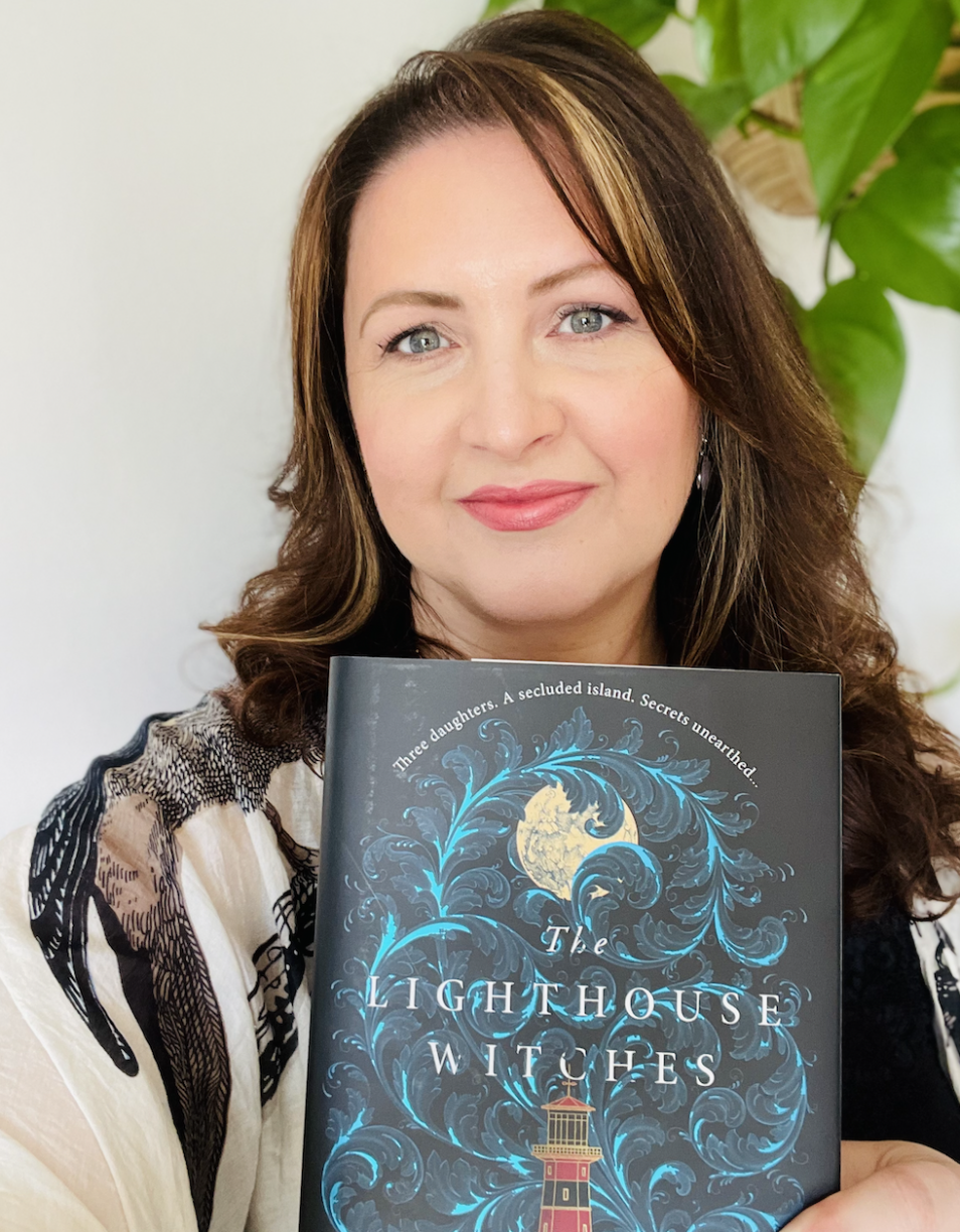 CJ Cooke, a white woman with dark brown hair, blue eyes and pink lipstick, smiles at the camera while holding a copy of The Lighthouse Witches